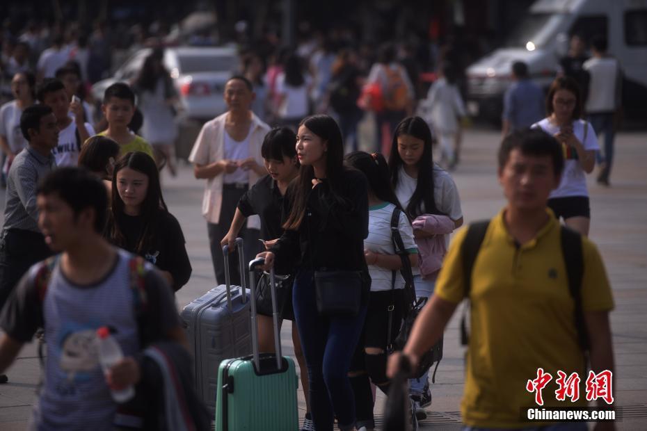 9月30日,重庆火车北站广场上众多旅客提着行李来来往往,迎来了国庆出行客流高峰。陈超 摄