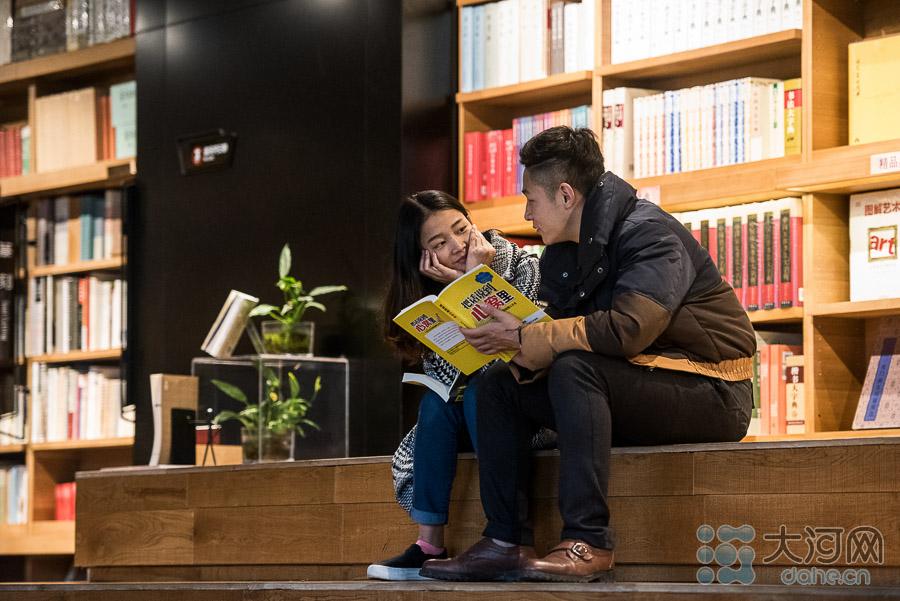 一对情侣将约会地点选在书店,同看一本书。