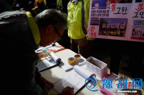 """10月29日晚,近两万名韩国民众及民间团体人士在首尔市中心举行烛光集会,谴责""""亲信干政事件""""给韩国社会带来的不良影响,要求总统朴槿惠对此事负责。图为民众在集会现场写下请愿书,要求查明事情真相。<a target=&apos;_blank&apos; href=&apos;http://www.chinanews.com/&apos;></table>中新社</a>记者 吴旭 摄"""