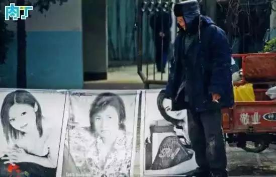 2004年,一名卖张贴画的男子在摊位前等待顾客。