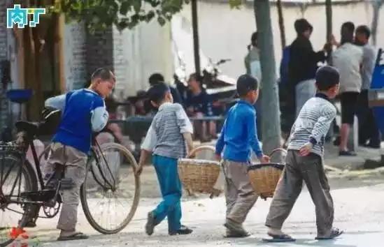 2004年,三名男孩抬着两筐物品到集市上出售。