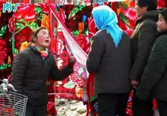 2004年,一名卖布的女摊贩在和顾客讨价还价。