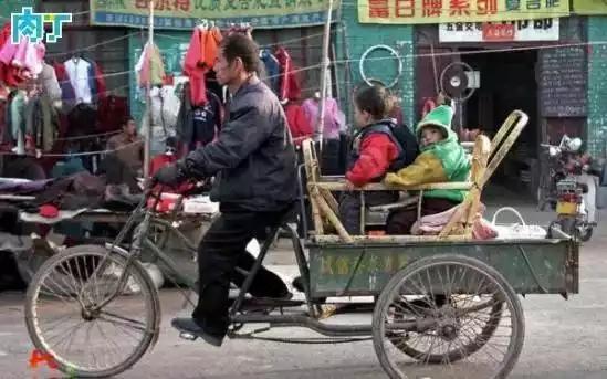 2004年,一名男子脚蹬载着两名孩子的三轮车逛集市。