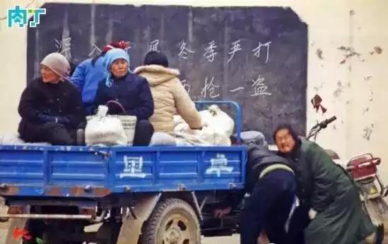 2003年,逛完集市后,两名男子在协力用摇把发动三轮车,准备载着家人回家。