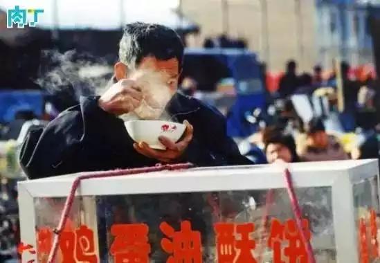 2004年,一名推着自行车流动卖油酥饼的男子正在喝一碗从小摊上买的热汤。