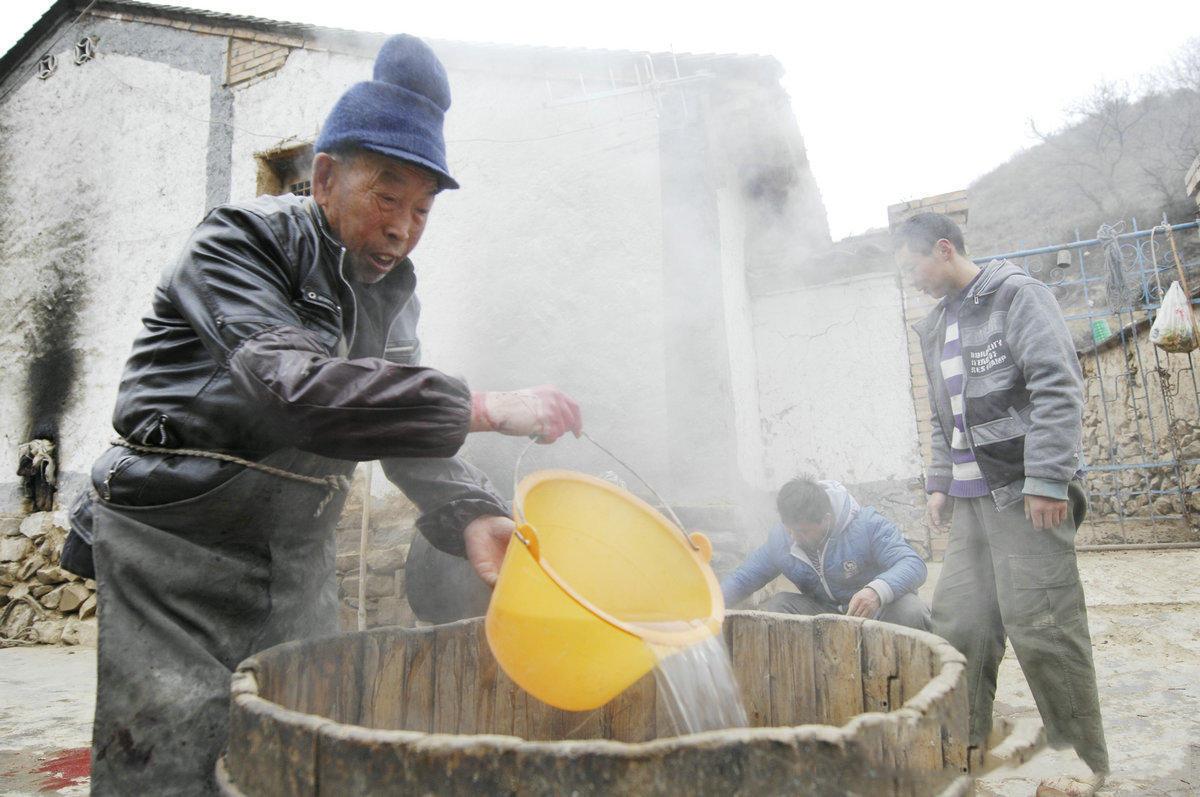 一口大木桶,汽油桶里的水烧开了,木桶里放半桶水,把放过血的猪丢木桶里,先拿高粱做的扫把给死猪全身撒上热水。