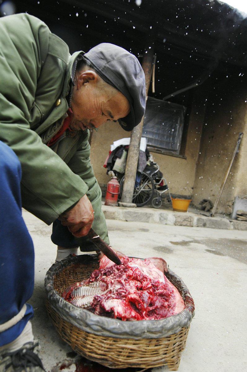 这位大叔抢到了猪头,正在研究回家怎么做着好吃,有人说吃啥补啥,猪脑子农民们却是不吃的,都说那是骂人的,吃了会变笨。