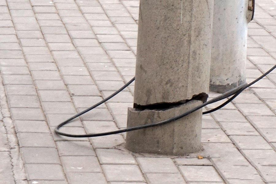 12月14日上午9时许,在华山路与岗坡路交叉口向南约50米道路西半幅公交站台附近,安装在华山路北向南的快慢车道之间紧挨着的两根水泥线杆全部从根部完全断裂后,斜靠在旁边的一根路灯杆(北边的那根)和一棵行道树枝叉上。