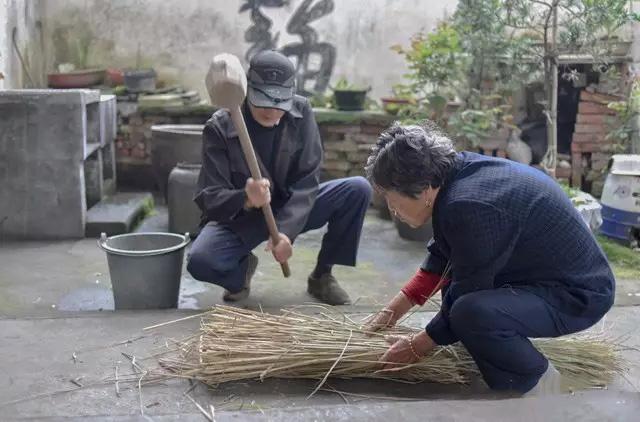 捶打稻草使之软韧。