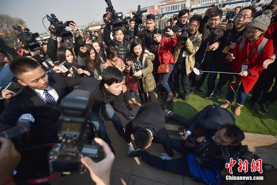 3月3日,全国政协十二届五次会议在北京人民大会堂开幕。刘翔委员俯身搀扶在追拍过程中跌倒的记者。中新社记者 金硕 摄