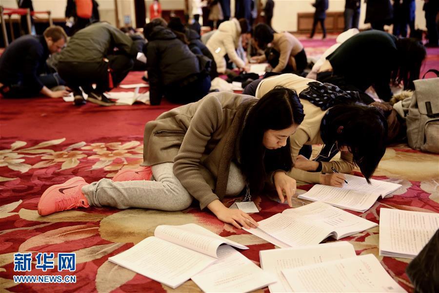 3月5日,第十二届全国人民代表大会第五次会议在北京人民大会堂开幕。这是记者在人民大会堂内领到报告后抓紧阅读。 新华社记者 金立旺 摄
