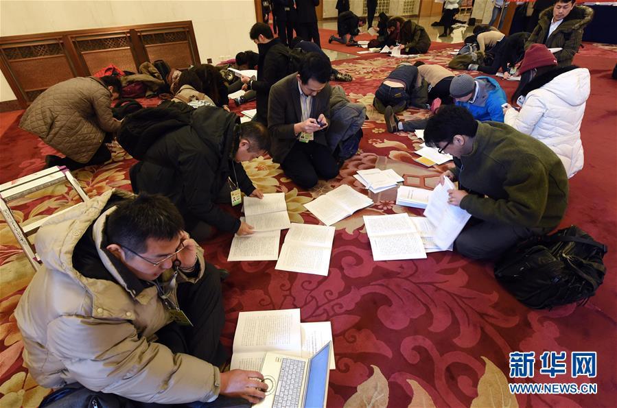 3月5日,第十二届全国人民代表大会第五次会议在北京人民大会堂开幕。这是记者在人民大会堂内领到报告后抓紧阅读。 新华社记者杨宗友摄