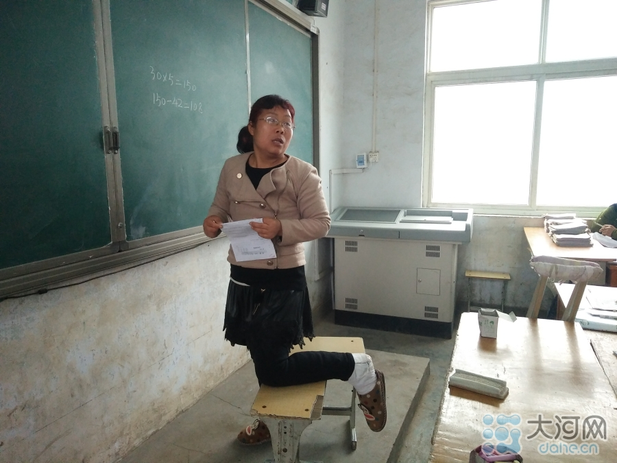 薛改霞打着石膏的左腿跪在凳子上,右腿着地,正在为学生们上课。