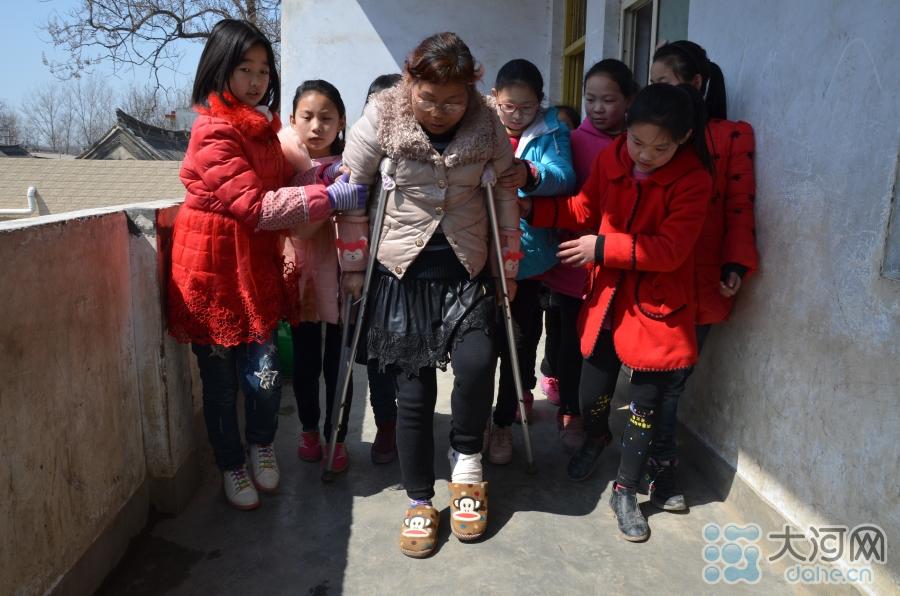 薛改霞拄着双拐,在学生们的帮助下吃力地行走着。这些照片被师生转发后,在当地引起了不小的轰动,大家一致评论:够敬业!真坚强!