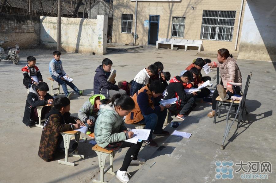 学校是寄宿制学校,中午天气不错,吃完午饭,薛老师把成绩不太好的几名同学集中在教学楼前的广场上,给大家补习功课。
