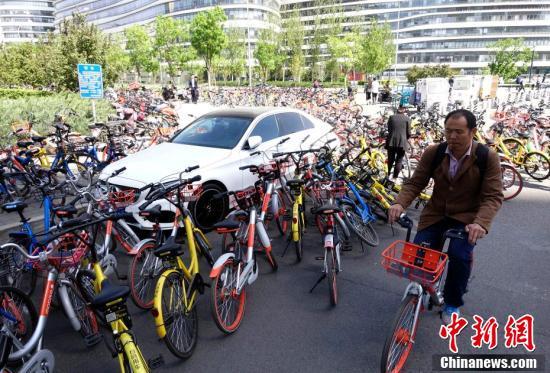 """4月18日,北京,一辆私家车被各家公司、不同颜色的""""共享单车""""包围。近来,""""共享单车""""在方便市民出行的同时,缺乏停车管理等问题也逐渐显现。 中新社记者 侯宇 摄"""