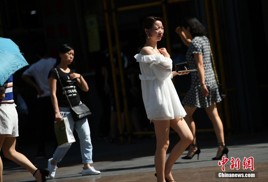 5月17日,观音桥步行街上美女着凉装出行。据中央气象台消息,17日-19日,北方多地将遭遇今年以来首次大范围高温天气,涉及京津冀、内蒙古等7省市区,其中18日高温范围最广、强度最大,内蒙古东部偏南地区局地更有可能出现38-40℃的最高气温。中新社记者 陈超 摄