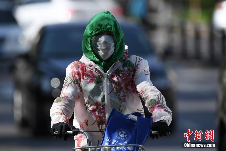 """5月17日,山西太原,民众在烈日下""""全副武装""""出行。据中央气象台消息,17日-19日,北方多地将遭遇今年以来首次大范围高温天气,涉及京津冀、内蒙古等7省市区,其中18日高温范围最广、强度最大,内蒙古东部偏南地区局地更有可能出现38-40℃的最高气温。武俊杰 摄"""