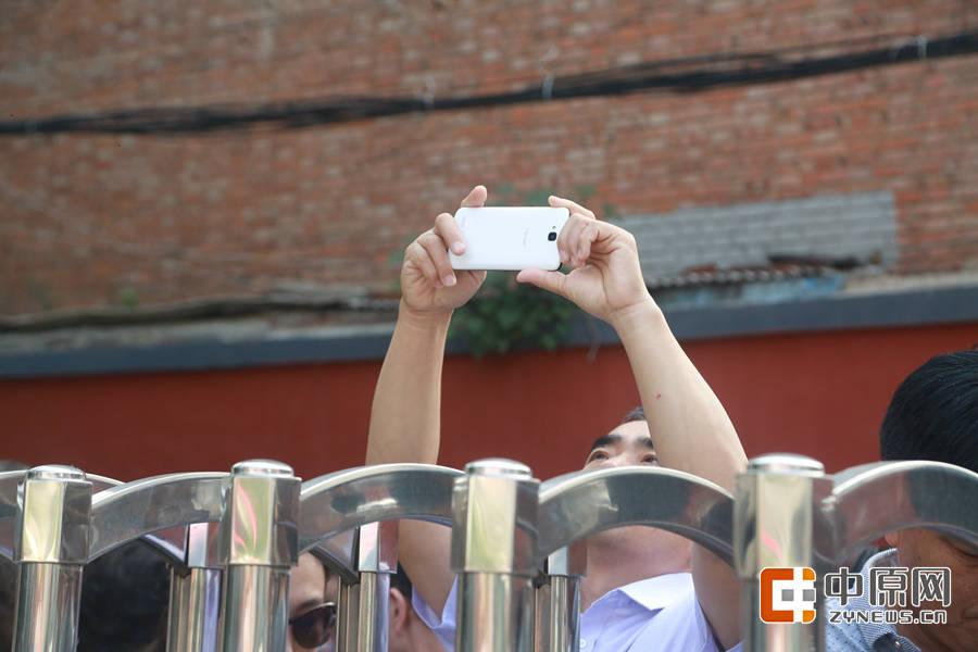 高高举起的手机,是为了拍到远去的孩子。