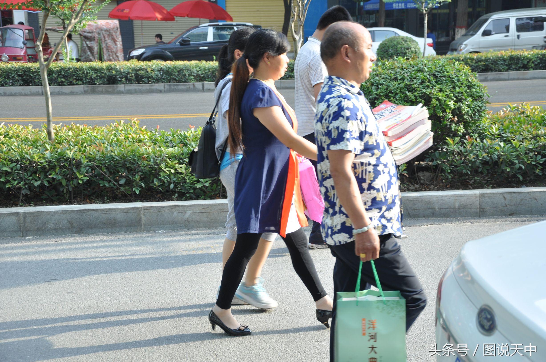 女儿参加高考,父亲抱着厚厚的复习资料陪同。