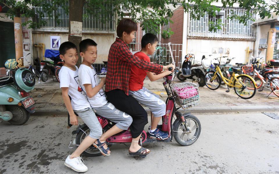 每天早上,马艳丽会分两批送孩子上学。第一趟后面带两个,前面蹲一个,送完以后再返回来接另外两个。