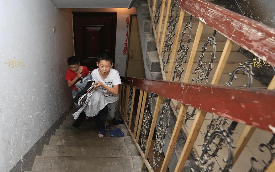 租住的地下室没有阳台,更没有阳光。衣服洗过后,孩子拿到院子里去晾晒。