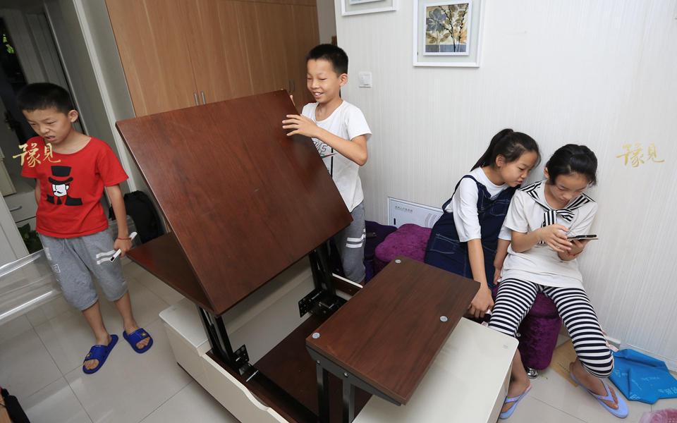 多功能茶几和餐桌,一定程度上解决了空间狭窄的困局。开饭前,孩子们熟练地支起了餐桌。