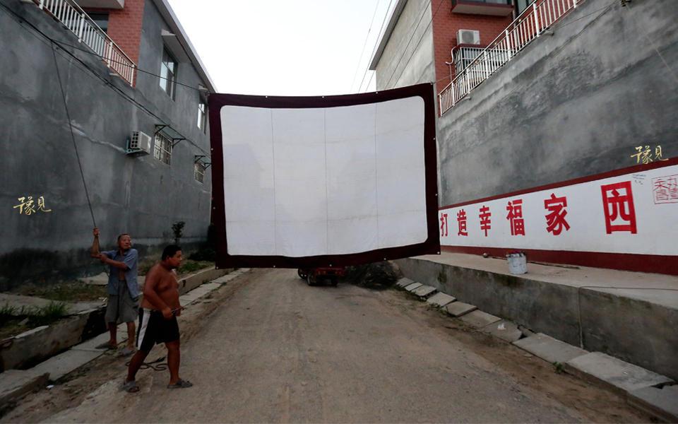 拉银幕、扯电线、上胶片……一番忙碌后,村民带着小板凳陆续到来,静候电影的开始。
