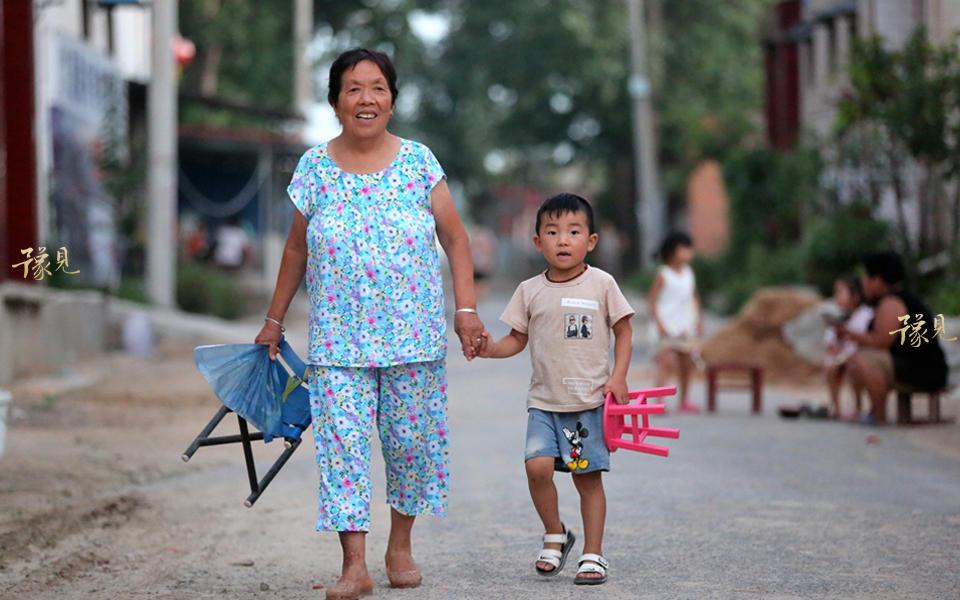 村民李大娘为了观影的时候占个好位子,早早的拉着孙子带着小板凳过去。