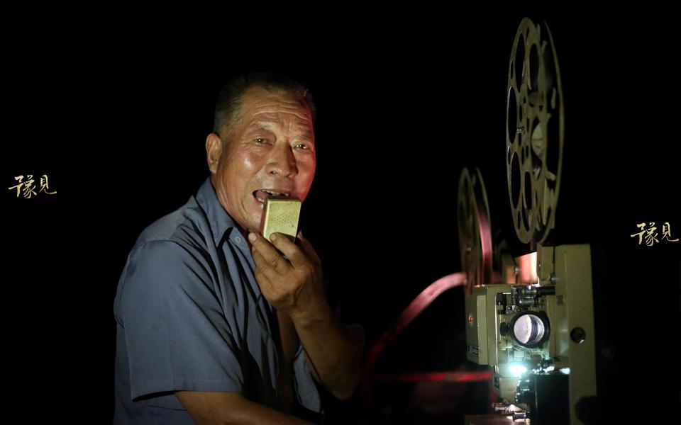 """村里有人家庭困难办喜事丧事时,鲁中德要么少要钱要么免费放映。有时村里老人对鲁中德说,晚上没事放场电影 他也会豪爽的答应。""""我现在很知足了,过去放映电影条件更艰苦,放映设备、发电机等上百斤的器具都是人背马驮。""""鲁中德回忆道,碰到暴雨的时候自己就拿塑料袋遮挡一下继续赶路。图为晚上十一点,电影放映结束。鲁中德手拿话筒大声的说:""""今天电影放映结束,今天电影放映结束""""。这时人群才散去,各回各家。"""