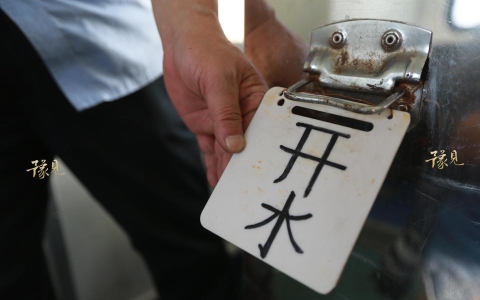 由于旅客经常找不到水包的位置,老崔自己动手写了开水两个挂在水包上。