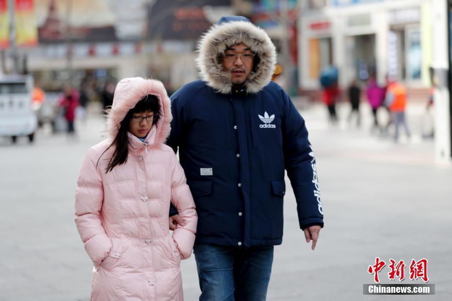 """11月29日,受冷空气影响,北京急速降温,迎来今年下半年迄今最冷的一天,最高气温降至1℃,最低气温-6℃,民众全副""""武""""装防寒出行。 中新社记者 杜洋 摄"""