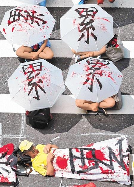 """台湾劳工团体带着红漆写的""""累""""字血布,在台当局立法机构前抗议。台湾《旺报》资料照片"""