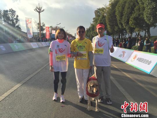 图为彭斌、胖虎及志愿者在上合昆明国际马拉松赛场 陈静 摄