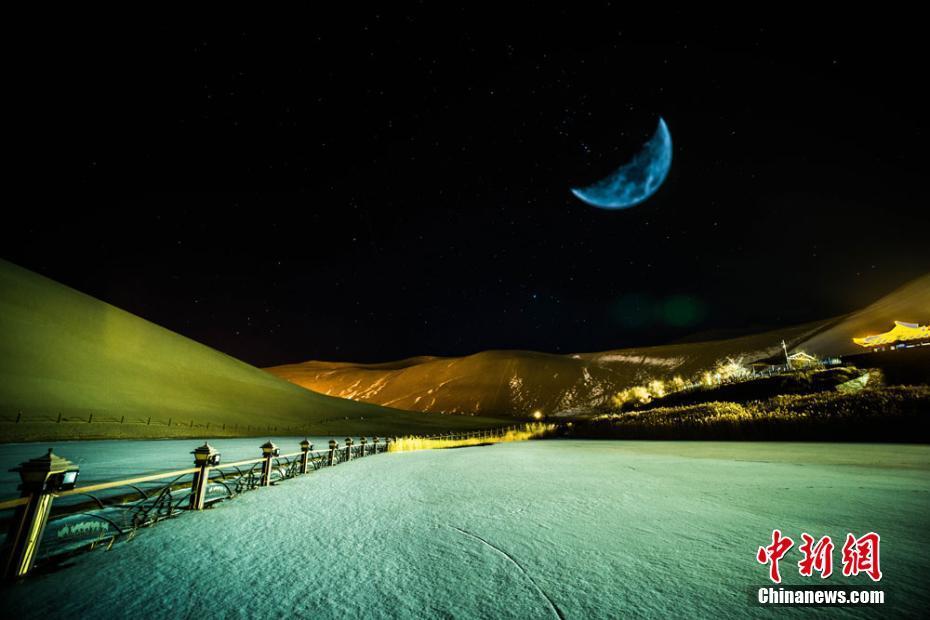 """几天前,甘肃敦煌大漠迎来新年首场降雪,随着近日积雪逐渐消融,当地著名的鸣沙山月牙泉景区呈现出如梦似幻的大漠雪景。夜幕降临,一弯如钩弦月悬挂在月牙泉上空,给敦煌大漠增添了梦幻迷人的大漠""""冬趣""""。(多重曝光) 王斌银 摄"""