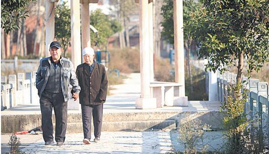 居民在通往湖边小亭子的路上悠然散步。