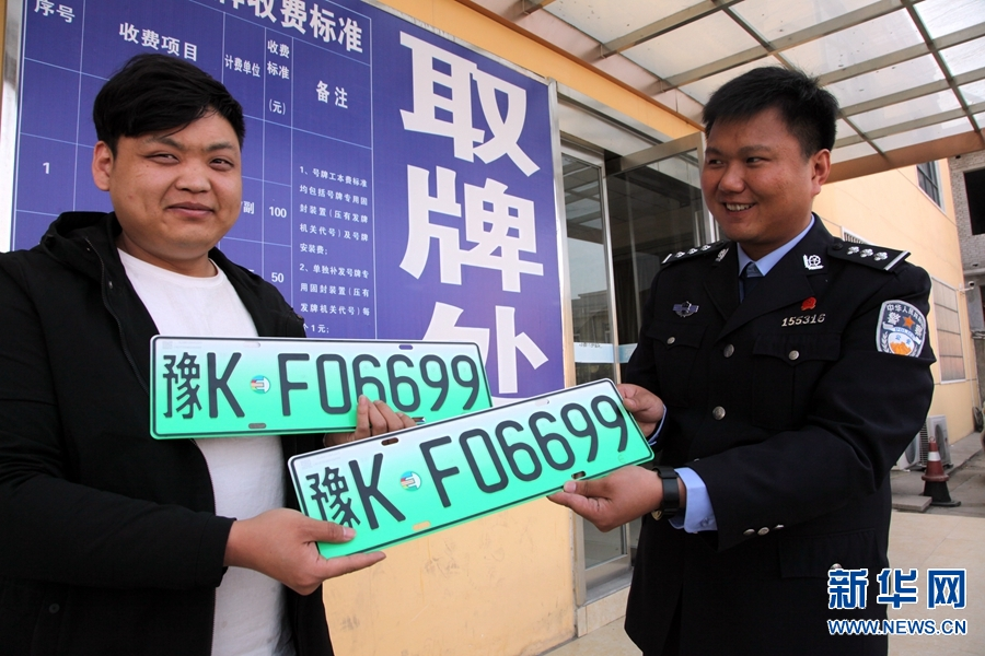 4月10日,河南许昌,车主左海从民警手中接过许昌市首副插电式混合动力汽车车牌。