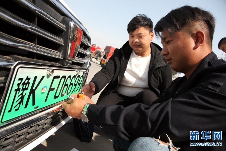 2018年4月10日,河南许昌,工作人员为车主左海安装许昌市首副插电式混合动力汽车车牌。