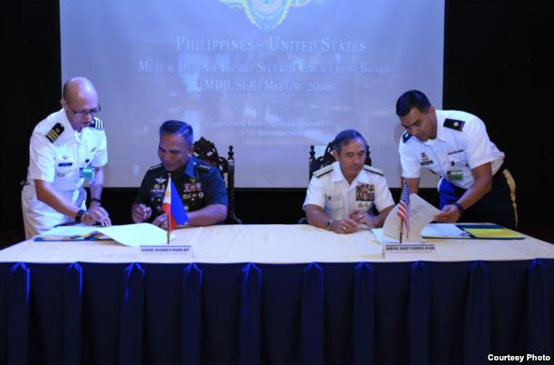 22日,哈里斯(右)与菲武装部队总参谋长(左)签署相关协议。