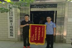 消费者送锦旗到二七区工商质监局侯寨所对工作人员表示感谢