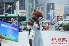 郑州公交车长街头化身小熊 拥抱市民开展乘客满意度调查