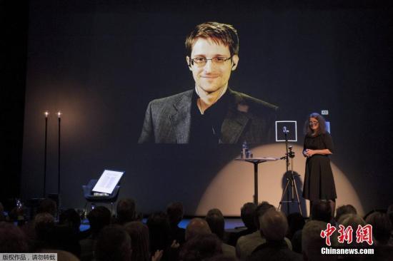 """资料图:2015年9月5日,挪威莫尔德,美国情报机构前雇员斯诺登被授予""""比昂松言论自由奖"""",大屏幕展示他的照片,一张空椅子代表他领奖。"""