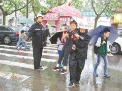 暴雨突袭郑州致路段积水 巡防员抱起小学生护送过马路