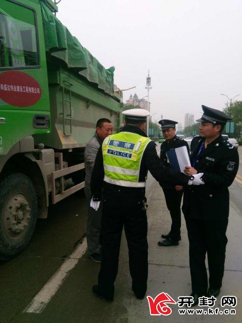 执法人员对建筑垃圾运输车进行检查。